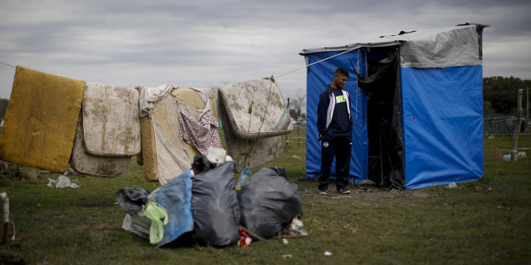 Jorge Gomez stands beside his makeshift home at a squatters camp in Guernica, Buenos Aires province, Argentina, Thursday, Oct. 1, 2020. A court has ordered the eviction of families who are squatting here since July, but the families say they have nowhere to go amid the COVID-19 pandemic. (AP Photo/Natacha Pisarenko)