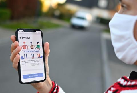 """A woman wearing a face mask holds a smartphone showing the new """"TousAntiCovid"""" application in Rennes, western France, on October 22, 2020, as several departments were put in """"maximum alert"""" and new curfew measures put in place in order to curb the spread of the Covid-19 (the novel coronavirus). The """"StopCovid"""" contact tracing application, which has been controversial and little used since its release on June 2, has been relaunched on October 22 in a new form and renamed """"TousAntiCovid"""". / AFP / DAMIEN MEYER"""