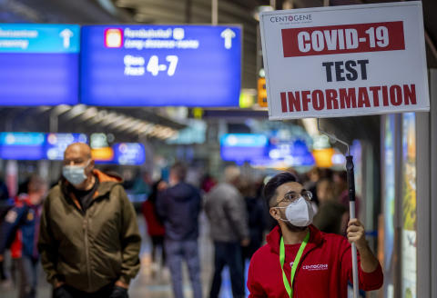 A man holds a sign leading the way to a Covid-19 test center the airport in Frankfurt, Germany, Thursday, Oct. 22, 2020. (AP Photo/Michael Probst)