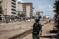 Ce 23 octobre à Conakry, capitale de la Guinée, un policier regarde un manifesteant qui jette des pierres. / AFP / JOHN WESSELS