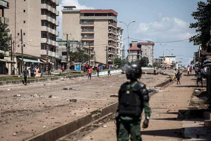 Ce 23 octobre à Conakry, capitale de la Guinée, un policier regarde un manifestant lancer des pierres.  / AFP / JOHN WESSELS