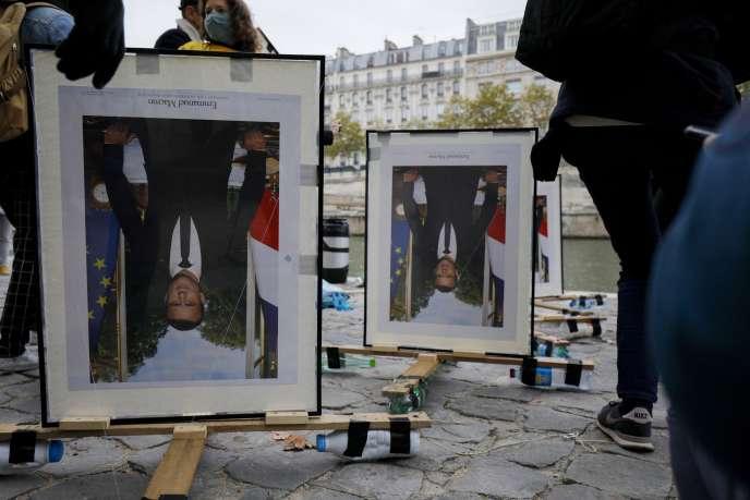 Des militants d'ANV-COP21 (Action non violente-COP21) attachent des portraits à l'envers d'Emmanuel Macron, sur les quais de la Seine, à Paris, le 15 octobre 2020. Ils soutiennent ainsi les « décrocheurs »,six activistes d'Action climat Paris, du portrait d'Emmanuel Macron dans des mairies parisiennes.