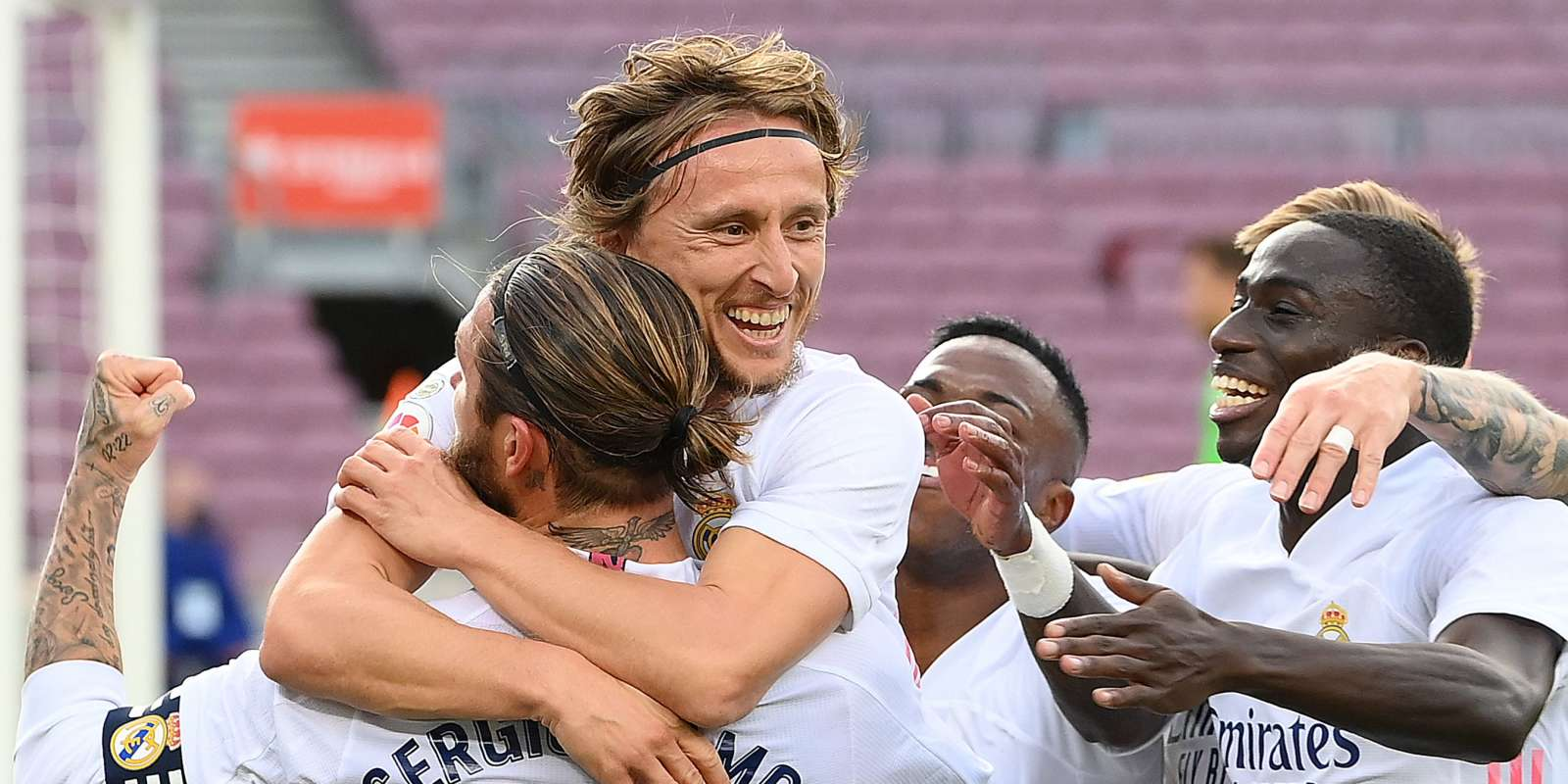 Real Madrid's Croatian midfielder Luka Modric (C) celebrates with teammates after scoring a goal during the Spanish League football match between Barcelona and Real Madrid at the Camp Nou stadium in Barcelona on October 24, 2020. / AFP / LLUIS GENE