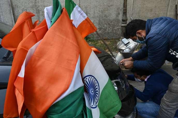 Un militan du BJP, le parti nationaliste hindou au pouvoir en Inde, dispose le drapeau national pour décorer une voiture avant une manifestation à Srinagar, dans leJammu-et-Cachemire, lundi 26 octobre.