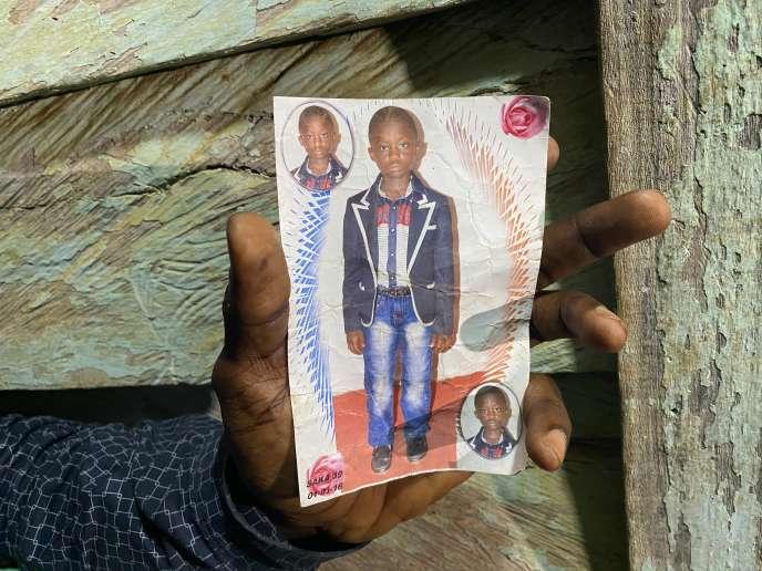 Le pasteur Boniface Tamangoua Ngamenyi montre la photo de son fils, Victory Camibon, 11 ans, tué lors de l'attaque du 24 octobre 2020 à Kumba, dans la région anglophone Sud-Ouest du Cameroun.