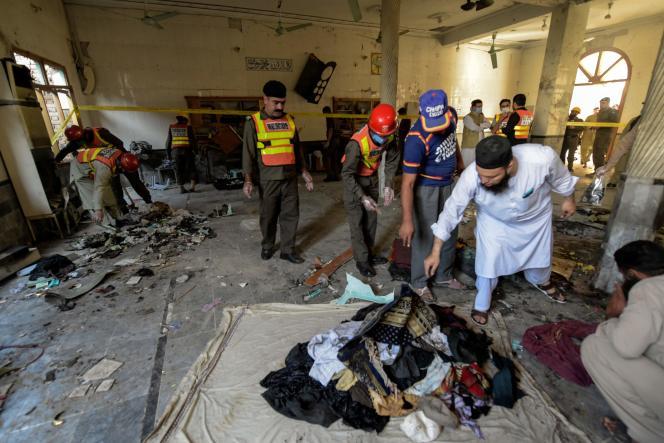 Des sauveteurs collectent des biens après l'explosion qui a frappé une école religieuse de Peshawar, mardi 27octobre.