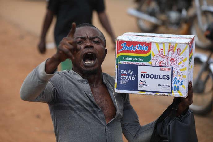 Un homme transporte un paquet de nouilles estampillé « Cacovid », lors d'un pillage d'un entrepôt, à Abuja, le 26 octobre 2020.
