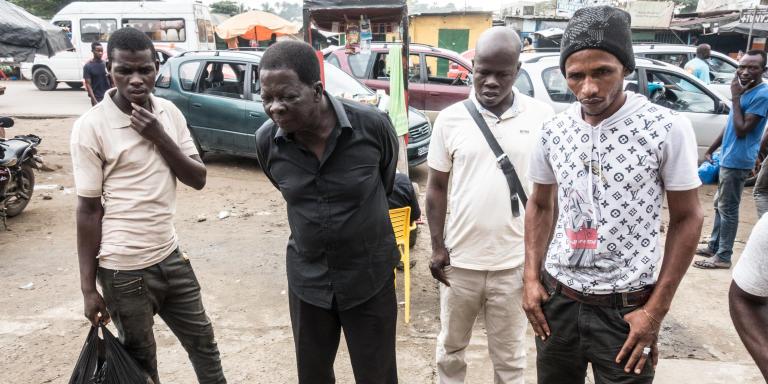 «Les Titrologues» fait référence à une expression populaire à Abidjan, qui désigne l'ensemble des couches socioprofessionnelles ivoiriennes arrêtées devant un kiosque à journaux, qui lisent, chaque jour sauf le dimanche, la plupart du temps debout, titres et manchettes de l'ensemble des journaux ivoiriens, toutes tendances politiques confondues. Cette lecture collective des unes de la presse écrite ivoirienne débute généralement dès 6H30 du matin, sur le trajet qui sépare son travail de sa maison. Elle a lieu dans un silence circonscrit au kiosque et donne parfois lieu à des débats mais à très peu d'achat de journaux papiers.   Série photographique réalisée, du 20 au 29 Octobre 2020, autour du kiosque à journaux tenu par Salif aux 220 logements à Adjamé, un quartier populaire d'Abidjan.