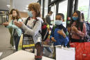 Pupils use hand sanitizer as they walk in the Europeen school of Strasbourg, eastern France, on September 1, 2020 at the start of the new school year amid the Covid-19 epidemic. - French pupils go back to school on September 1 as schools across Europe open their doors to greet returning pupils this month, nearly six months after the coronavirus outbreak forced them to close and despite rising infection rates across the continent. (Photo by FREDERICK FLORIN / AFP)