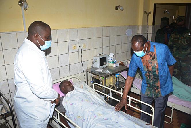 Le président guinéen Alpha Condé (à droite) rend visite à un policier à l'hôpital de Conakry, le 28 octobre 2020.