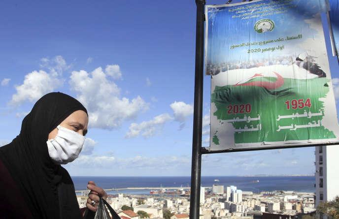 Une femme marche devant des affiches promouvant le vote pour le prochain référendum, à Alger,le 27 octobre.
