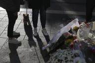 Des personnes se tiennent près de fleurs, de messages et de bougies devant l'église Notre Dame, à Nice, le vendredi 30 octobre 2020.