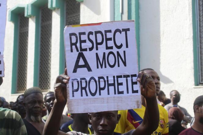 Un homme brandit une pancarte lors d'un rassemblement devant la grande mosquée de Bamako, le 28 octobre 2020, pour condamner les propos du président Emmanuel Macron, qui a défendu les valeurs laïques et le droit de se moquer de la religion.