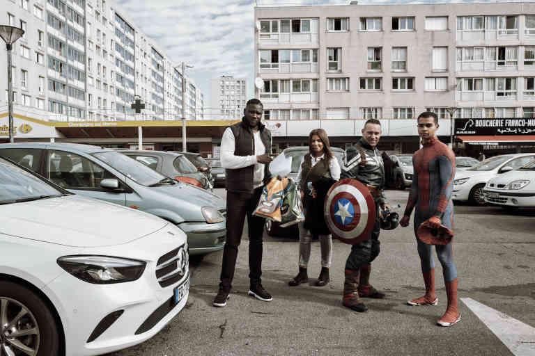 Champigny sur Marne, à l'extérieur des locaux du taxiphone SmartAccessory, sur la dalle HLM, Place Rodin. Avant de partir pour visiter un enfant en fin de soins palliatifs, Mamadou, Chorouk (responsable de la communication), Igor (Captain America) et Kevin (Spider-Man) posent pour une dernière photo souvenir. la ligue des avengers de Paris est une association qui vient au chevet d'enfants malades déguisés en super-héros pour les distraire.   Photo : Julien DANIEL / MYOP