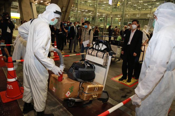 Les bagages d'un groupe de visiteurs chinois sont nettoyés pour arrêter la propagation du Covid-19, à l'aéroport de Suvarnabhumi, à Bangkok, le 20 octobre 2020. Ces voyageurs feront ensuite un séjour de quatorze jours dans un centre de quarantaine d'Etat.