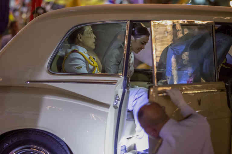 King Maha Vajiralongkorn, left and Queen Suthida, right get in to a limousine after meeting supporters in Bangkok, Thailand, Sunday, Nov. 1, 2020. Under increasing pressure from protesters demanding reforms to the monarchy, Thailand's king and queen met Sunday with thousands of adoring supporters in Bangkok, mixing with citizens in the street after attending a religious ceremony inside the Grand Palace. (AP Photo/Wason Wanichakorn)