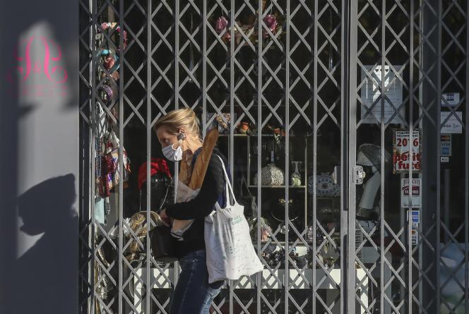 Une femme passe devant un magasin fermé, à Paris, en novembre 2020, pendant le deuxième confinement français.