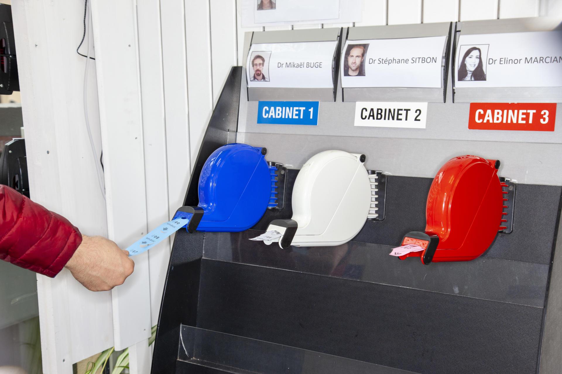 Le distributeur de tickets pour l'attente, chaque couleur correspond à un médecin généraliste, dans un cabinet du 19earrondissement de Paris.