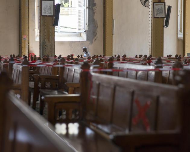 Un fidèle dans l'église Saint-Pierre-et-Saint-Paul de Pointe-à-Pitre, où le sens de circulation a été modifié et restreint pour limiter les risques pendant la crise sanitaire.