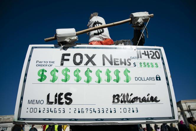 Protesta frente a las oficinas de Fox News el 4 de noviembre de 2020 en Washington, mostrando un cheque emitido por un