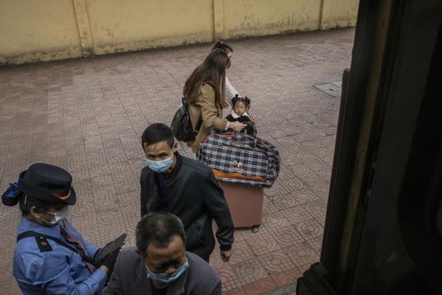 En gare de Yushan, une petite fille accompagnée de sa famille est descendue du train Guiyang-Shanghai alors que des passagers embarquent.