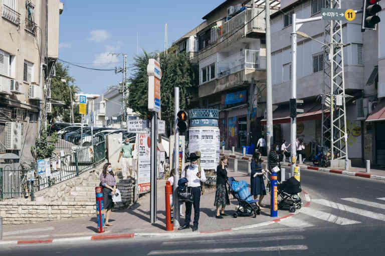 ISRAEL, Bnei Brak - The busy junction of Rabbi Akiva street with Jerusalem street in the center of Bnei Brak on Monday, November 02, 2020. In September 2020, Israel became the country with the highest rate of COVID-19 infections per capita and therefore approved a second country-wide lockdown, the world's first at the time. The ultraorthodox sector of the Israeli society has recorded the highest rate of infections, partly due to defiance of restrictions, but also due to crowded living conditions, and large religious or family-related gatherings. Some Jewish Orthodox religious leaders opted for opening religious school and synagogues in defiance of the rules, reportedly in order to stop an accelerated alienation of individuals from the orthodox community. (Jonas Opperskalski / laif)