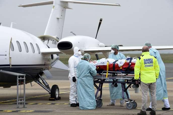 Le personnel médical du SMUR de Lille prend en charge un patient atteint du Covid-19 de l'hôpital de Roubaix pour un transfert vers l'hôpital de Münster, dans le nord de l'Allemagne, à l'aéroport de Lille-Lesquin, dans les Hauts-de-France, le 10novembre.