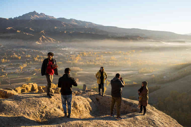 Young men and women, some from Kabul and others from Bamiyan, take photos of one another at Gholghola, and ancient fort city, as the sunrises over the Bamiyan Valley.