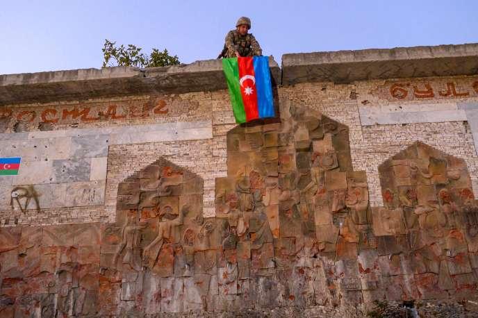 Un soldat suspend le drapeau de l'Azerbaïdjan à Jabrayil (Haut-Karabakh), où les forces azerbaïdjanaises ont repris le contrôle, le 16 octobre.
