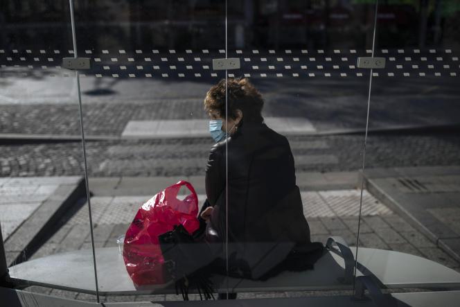 Une femme attend à une station de bus, à Paris, le 31 octobre.