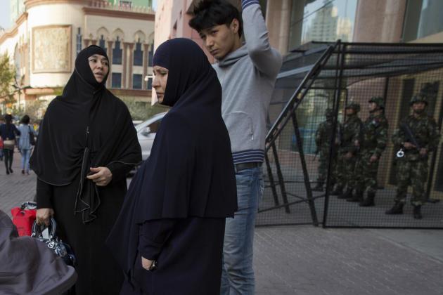 Musulmanes ouïgoures devant un poste des forces de sécurité, à Urumqi, capitale de la région autonome du Xinjiang, en mai 2014.