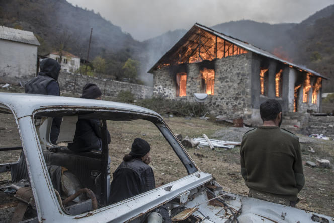 Une famille regarde sa maison qu'elle vient de mettre en feu avant de la quitter,Dadivank, Haut-Karabakh, le 12 novembre.