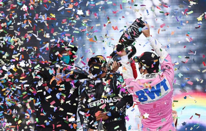 Le pilote mexicain Sergio Pérez et le patron de l'équipe Mercedes Toto Wolff entourent et baignent Lewis Hamilton sur le podium du Grand Prix de Turquie.