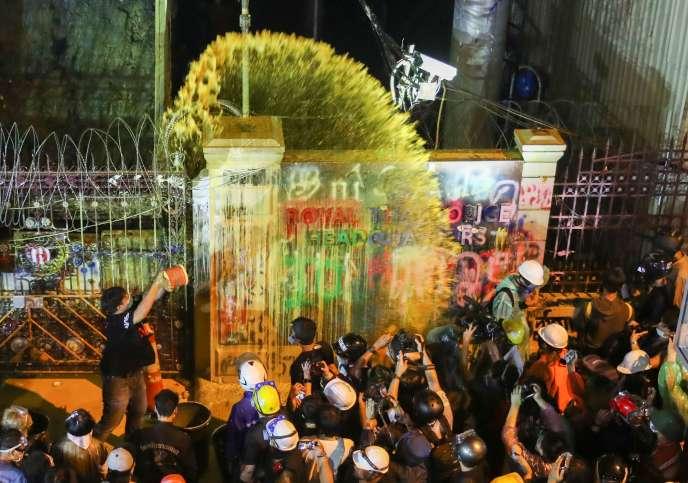 Un manifestant prodémocratie vide un pot de peinture sur la façade du quartier général de la police, à Bangkok, mercredi 18novembre.