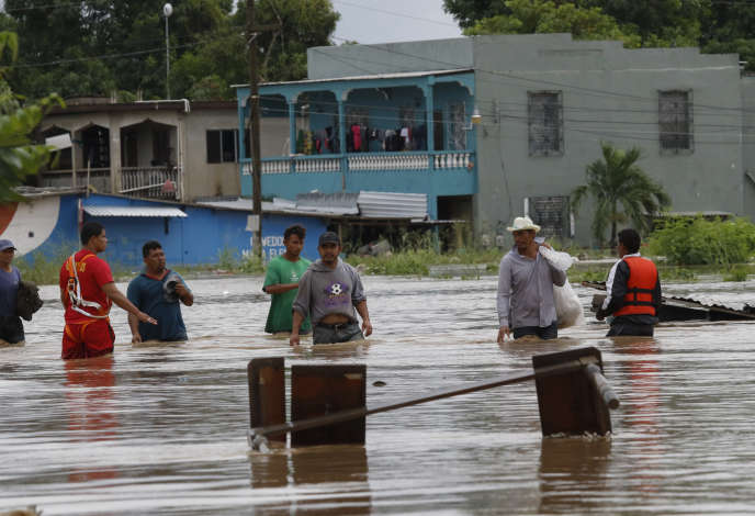 Des habitants dans une rue submergée de la ville de La Lima, au Honduras, le18novembre.