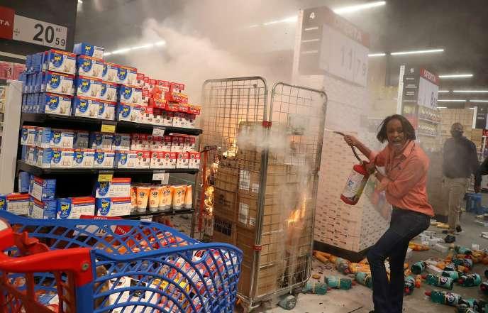 Un employé du groupe Carrefour tente d'éteindre un incendie provoqué par des manifestants qui ont attaqué ce supermarché de Sao Paulo, au Brésil.