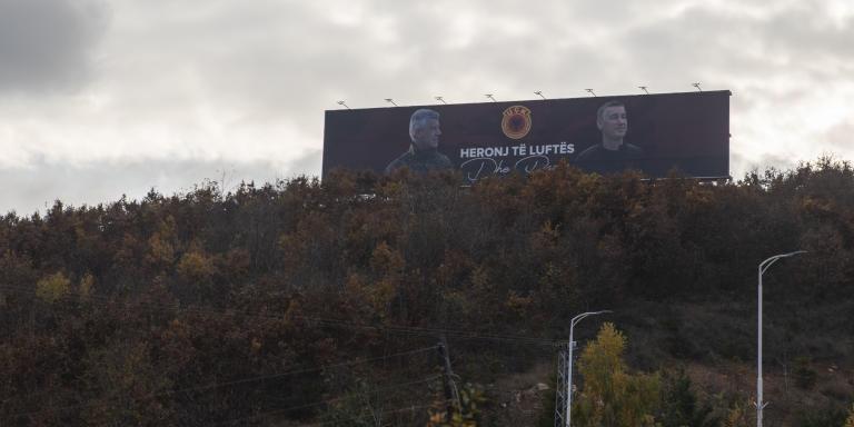 Portraits de l'ancien président Hashim Thaci et de l'ancien président du Parti démocratique du Kosovo Kadri Veseli vus sur un panneau géant au sommet d'une forêt.