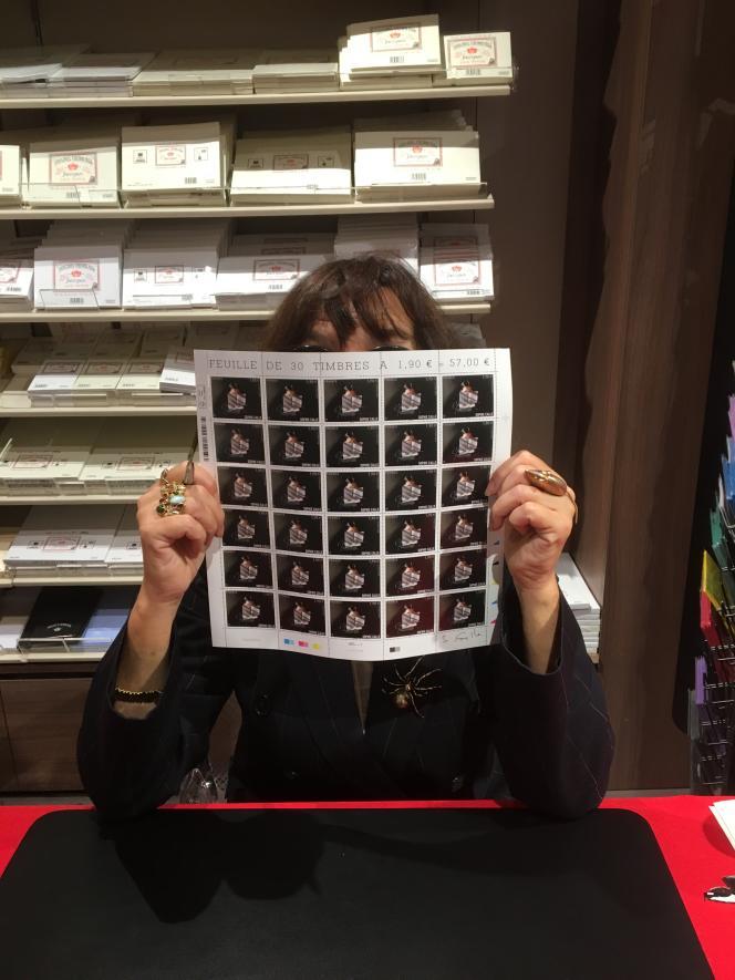 Sophie Calle et une feuille dédicacée de son timbre paru en 2018, au Carré d'Encre, à Paris.