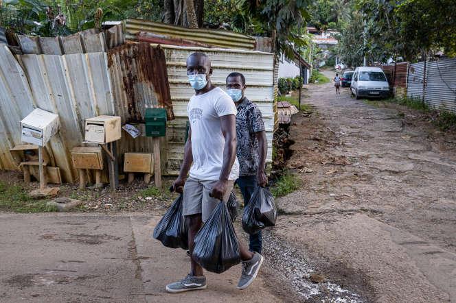 Des bénévoles distribuent des denrées alimentaires dans le bidonville Source de Baduel à Cayenne, le 7 juillet 2020.