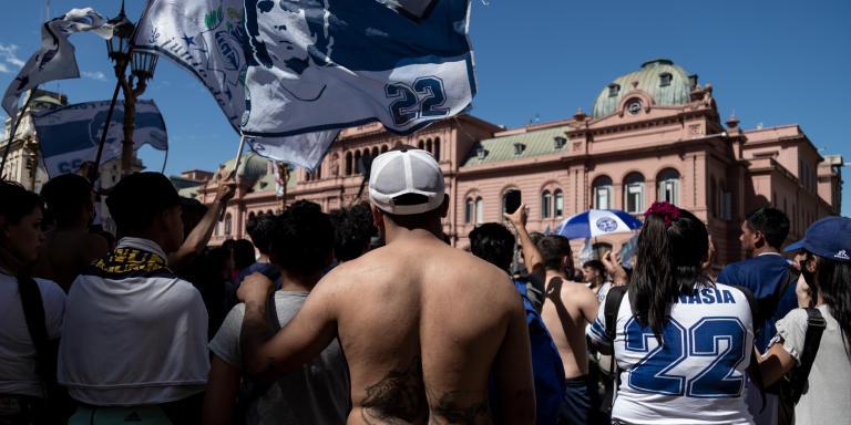 Des fans de Diego Maradona chantent et dansent alors qu'ils ne pourront pas pénétrer dans  la Casa Rosada pour faire un dernier adieu à leur idole, dont le cercueil est exposée aujourd'hui dans le palais présidentiel. Buenos Aires, Argentina. Anita Pouchard Serra pour Le Monde