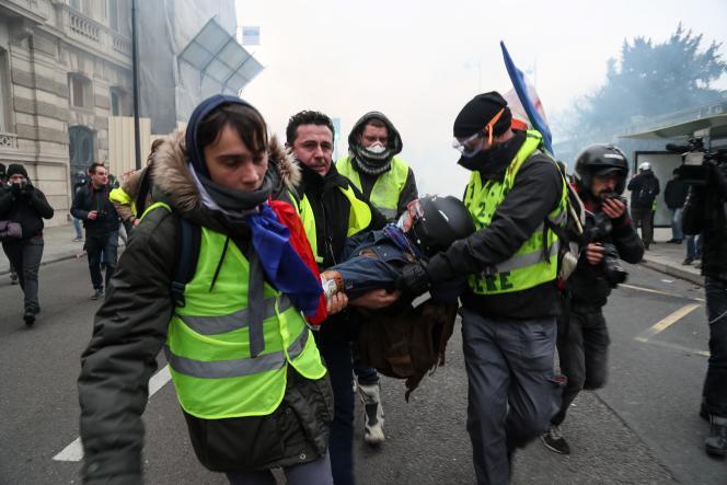 Des «gilets jaunes»transportent un photographe blessé, lors d'une manifestation à Paris, en 2019.