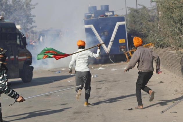 Des paysans sont pourchassés par la police, alors qu'ils tentaient de passer les barricades, le 27 novembre.