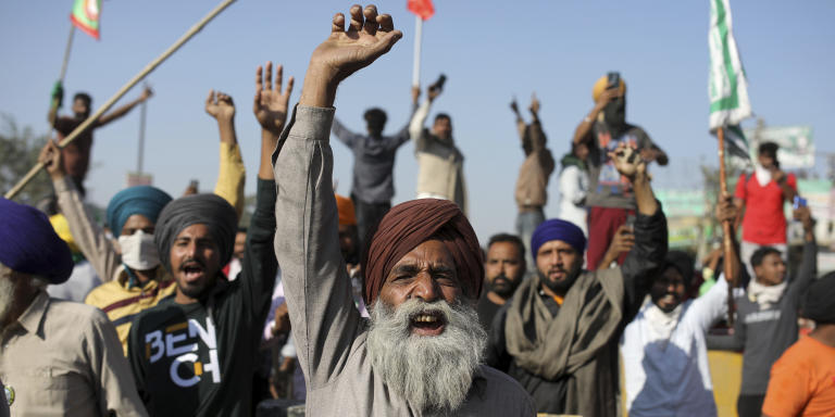 Protesting farmers shout slogans as they clash with policemen while attempting to move towards Delhi, at the border between Delhi and Haryana state, Friday, Nov. 27, 2020. Thousands of agitating farmers in India faced tear gas and baton charge from police on Friday after they resumed their march to the capital against new farming laws that they fear will give more power to corporations and reduce their earnings. While trying to march towards New Delhi, the farmers, using their tractors, cleared concrete blockades, walls of shipping containers and horizontally parked trucks after police had set them up as barricades and dug trenches on highways to block roads leading to the capital. (AP Photo/Altaf Qadri)