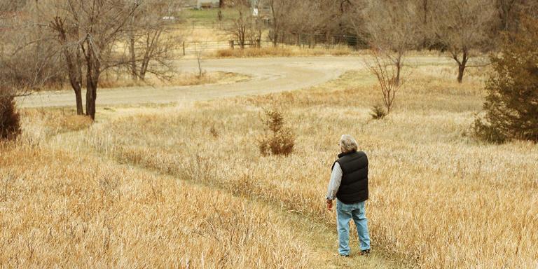 Wessington Springs, South Dakota, 26 November 2020. Doctor Tom Dean walking in his front yard in the foothills overlooking Wessington Springs.