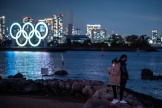 People stand on the shore as the Olympic rings are lit at the waterfront of Odaiba in Tokyo on December 1, 2020. / AFP / Philip FONG