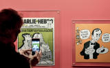 """A visitor takes pictures during a press visit of the exhibition """"Le rire de Cabu"""" at the City Hall in Paris on October 8, 2020, about French cartoonist Jean Cabut aka Cabu who was killed in the terrorist attack at the French satirical magazine Charlie Hebdo in 2015. (Photo by ALAIN JOCARD / AFP)"""