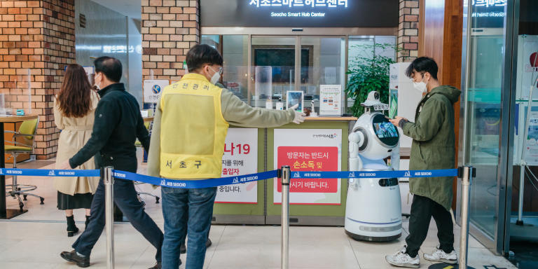 Upon entering the lobby of the Seocho District Office, visitors are guided to have their temperature measured by a robot and scan QR codes containing their personal information to aid with contact tracing, Seoul, South Korea, 20 Nov 2020.