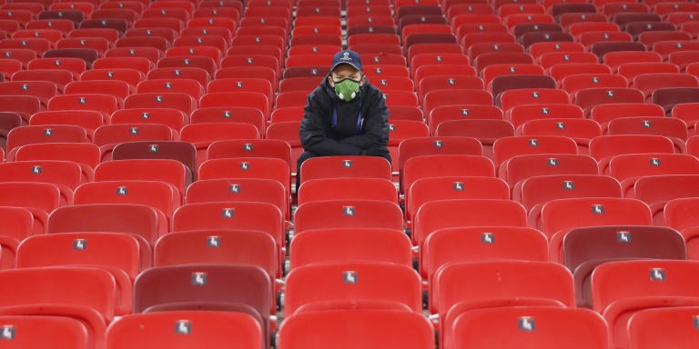 A technical staff sits on empty stands ahead of the Champions League group G soccer match between Ferencvaros and Barcelona at the Ferenc Puskas stadium in Budapest, Hungary, Wednesday, Dec. 2, 2020. (AP Photo/Laszlo Balogh)