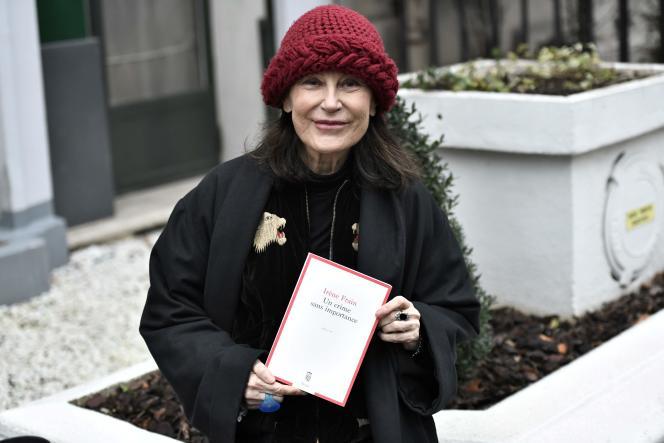 L'autrice française Irène Frain pose avec son livre « Un crime sans importance »,après avoir remporté le prix Interallié, devant le restaurant (fermé) Lasserre, à Paris, le 3 décembre 2020.
