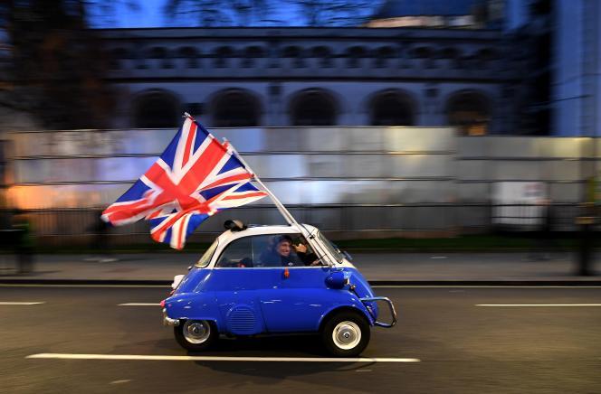 Un homme brandissant le drapeau du Royaume-Uni passe devant des partisans du Brexit, dans le centre de Londres, le 31 janvier 2020.